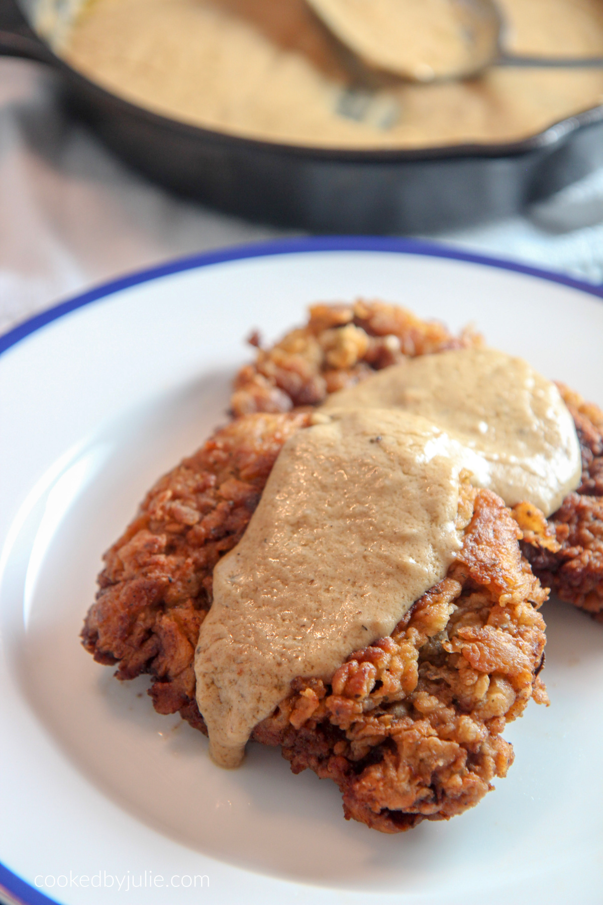 two pieces of chicken fried steak on a white and blue plate with gravy on top. An iron skillet with gravy and a spoon in the background.