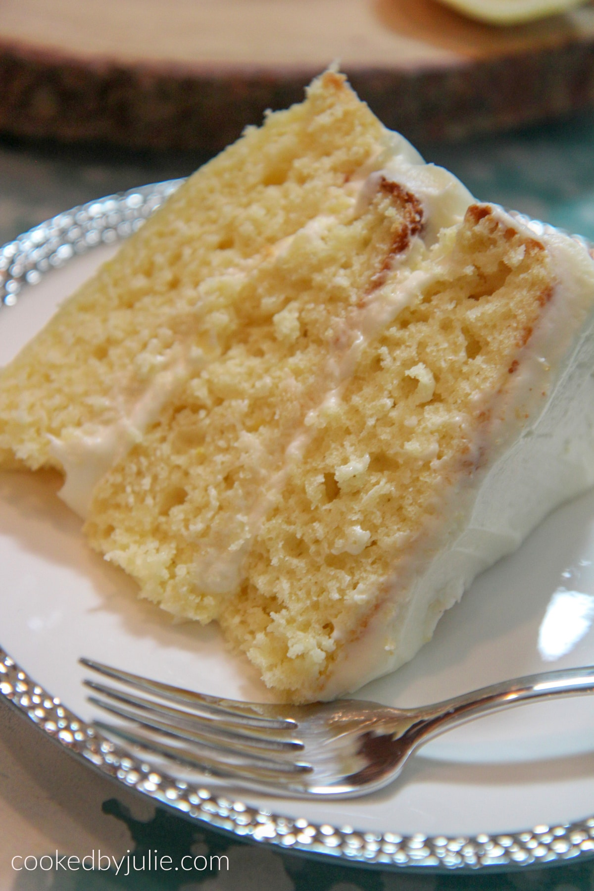 a three layer lemon cake slice on a white and sliver plate with a fork on the side.