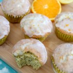 orange lemon poppy seed muffins on a wooden board with orange slices