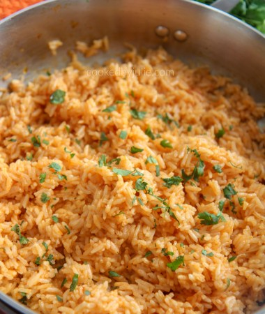 A skillet filled with Spanish rice with an orange kitchen towel and fresh cilantro in the background