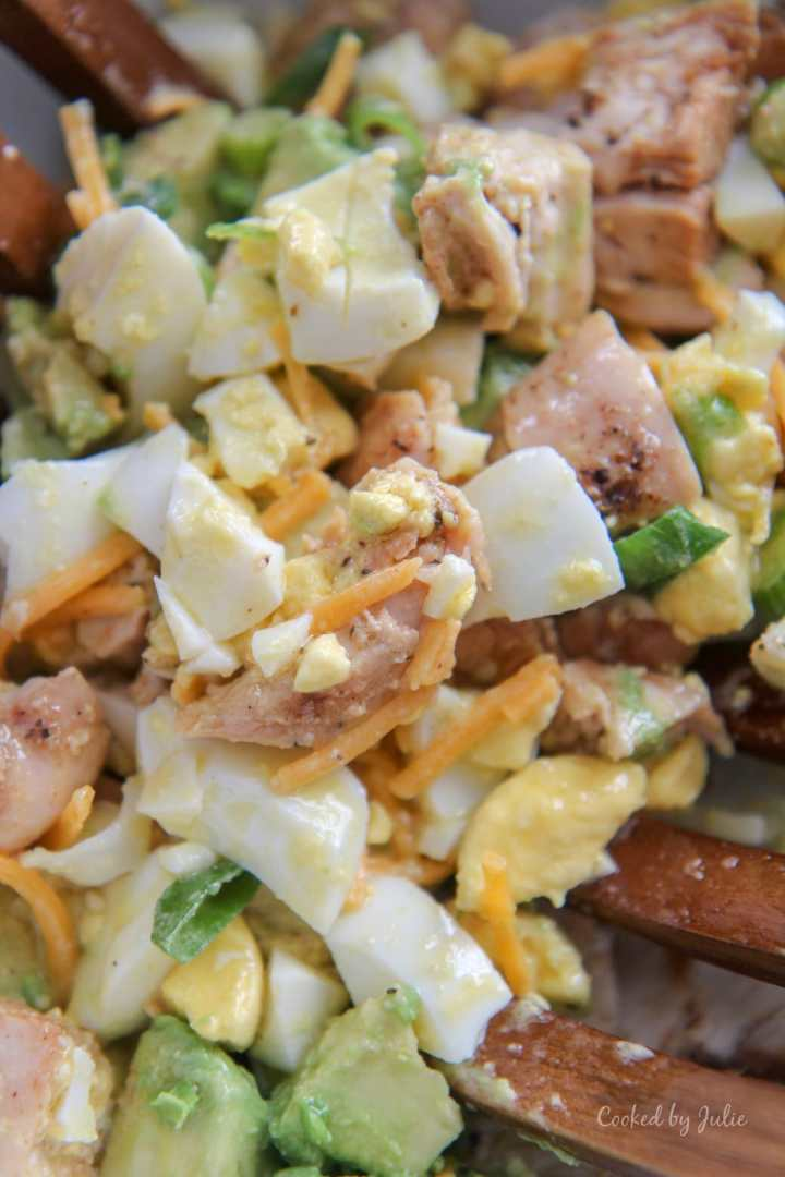 eggs, avocados, cheese, chicken, and scallions tossed in a lemon vinaigrette