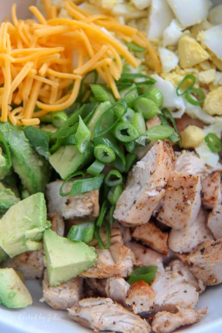 baked chicken, avocados, scallions, cheddar cheese, and boiled eggs in a white bowl