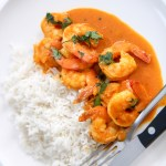 coconut shrimp curry with white basmati rice on a white plate with utensils