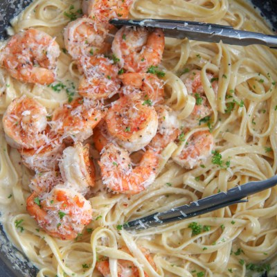 shrimp over fettuccine alfredo in a black skilletw ith tongs and fresh parsley