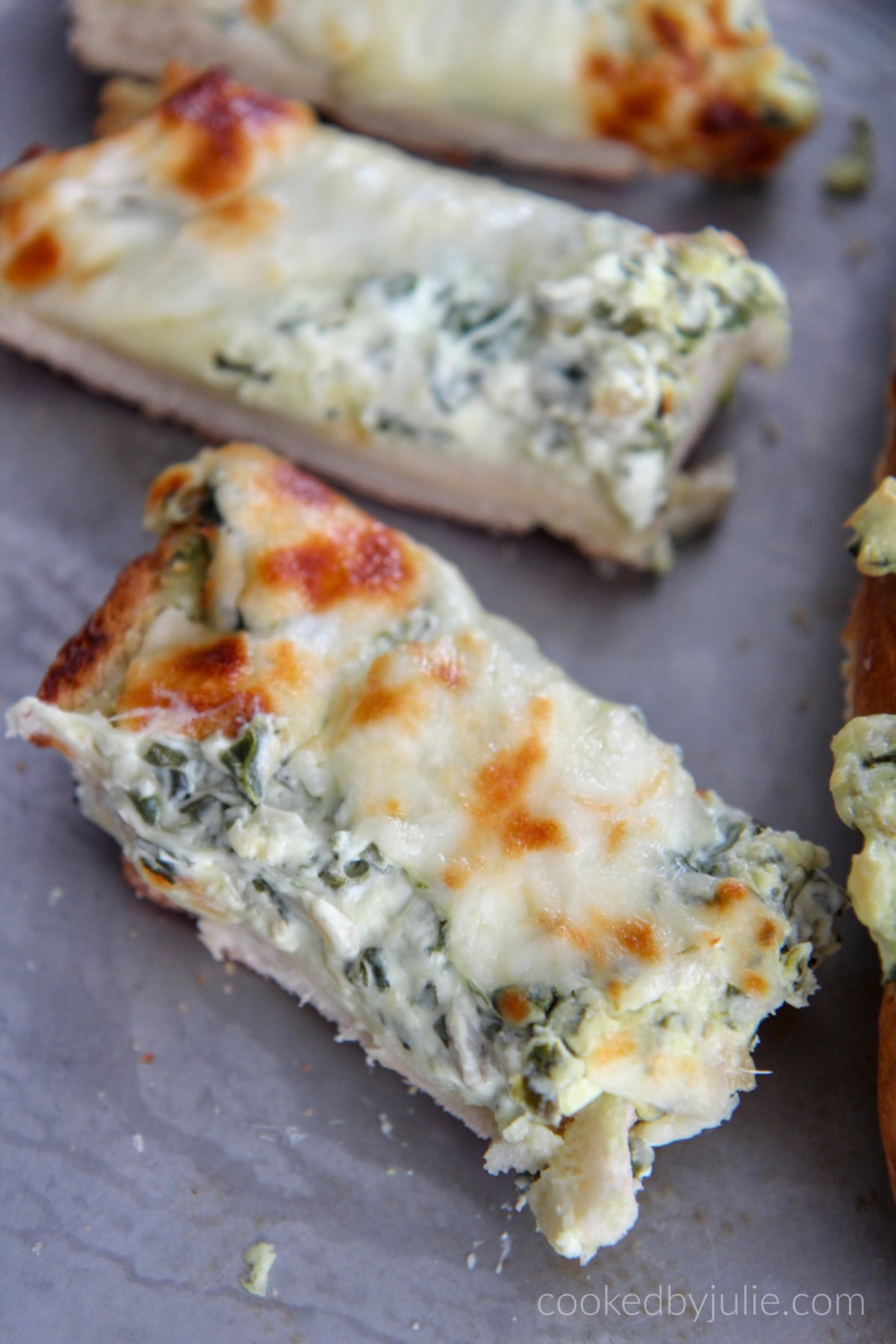 a couple slices of spinach artichoke cheese bread on a baking sheet