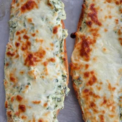 two loafs of cheesy spinach artichoke bread on a baking sheet
