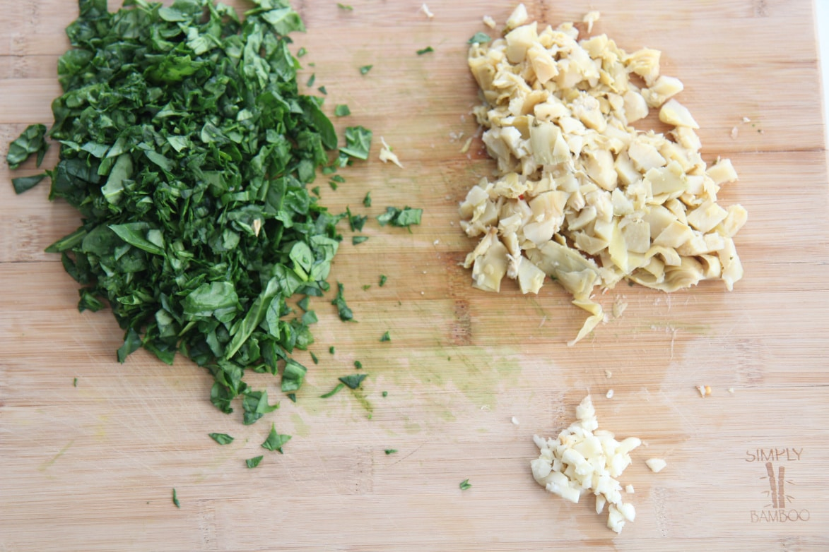fresh spinach, minced garlic, and roughly chopped artichokes on a wooden board