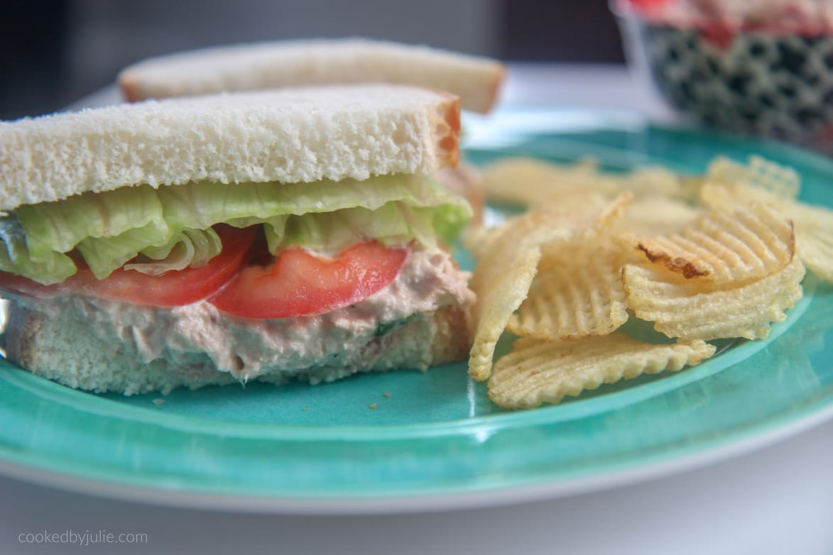 tuna salad sandwich with lettuce and tomato on a blue plate with potato chips