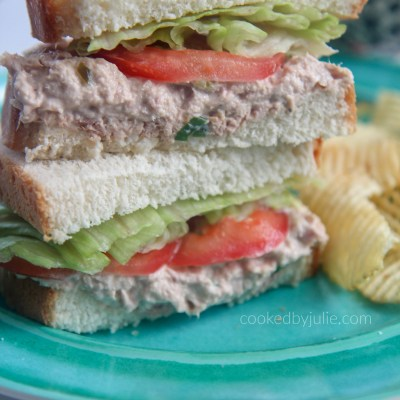 tuna salad sanwiches stacked on a blue plate with potato chips on the side