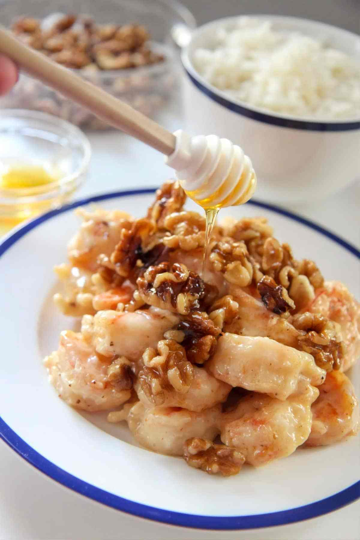 honey walnut shrimp on a white and blue plate with a honey dipper.