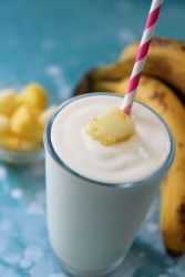 pineapple banana smoothie in a glass with a pink a white straw and fruit on top