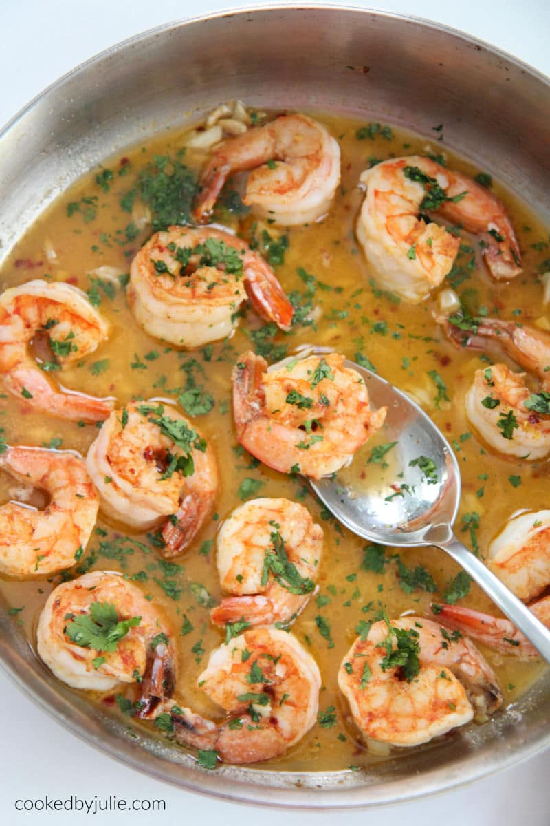 shrimp scampi in a skillet with a spoon and parsley