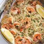 shrimp scampi spaghetti in a skillet with lemons and a spoon