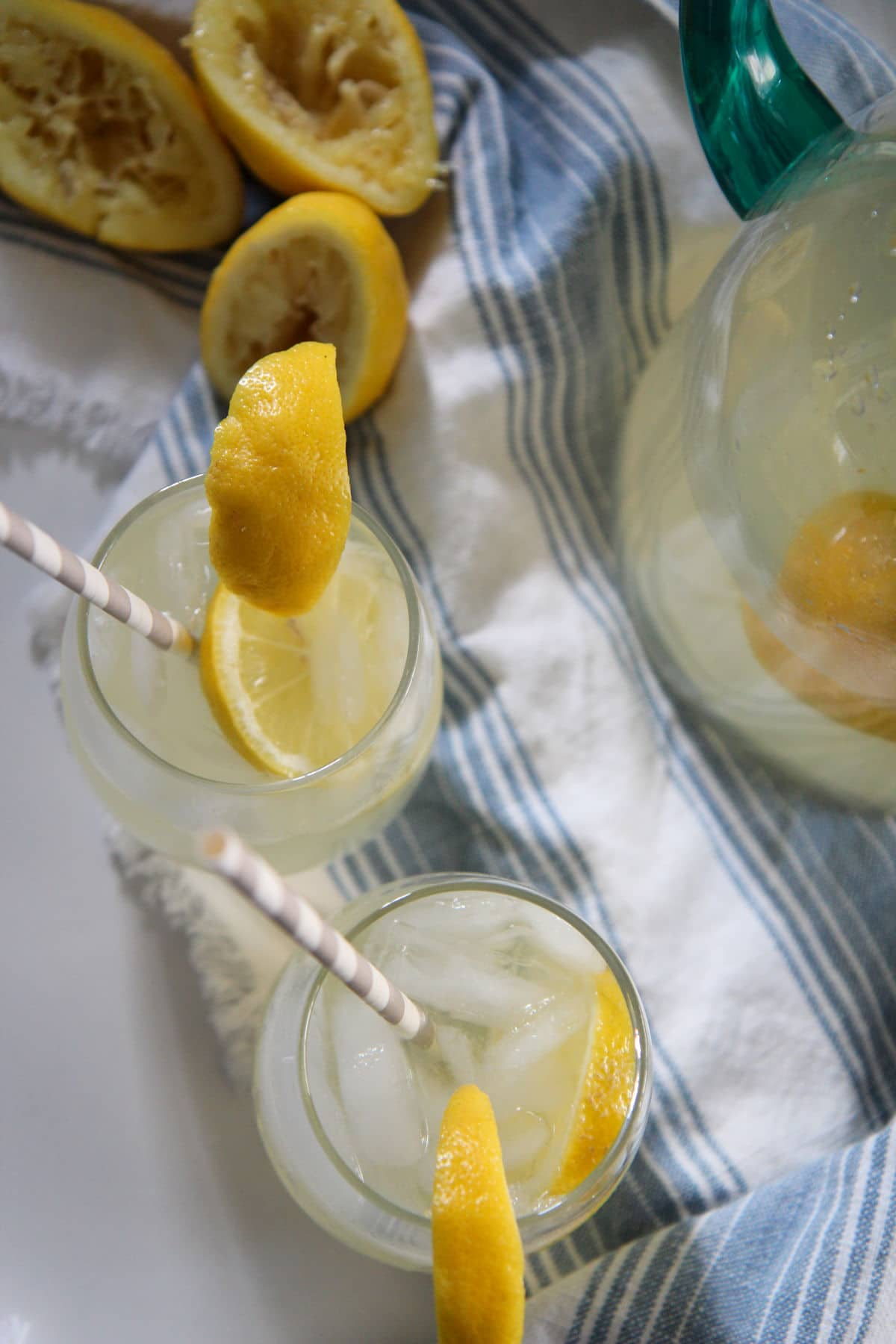 2 glasses of lemonade with straws on a white table with a blue table cloth