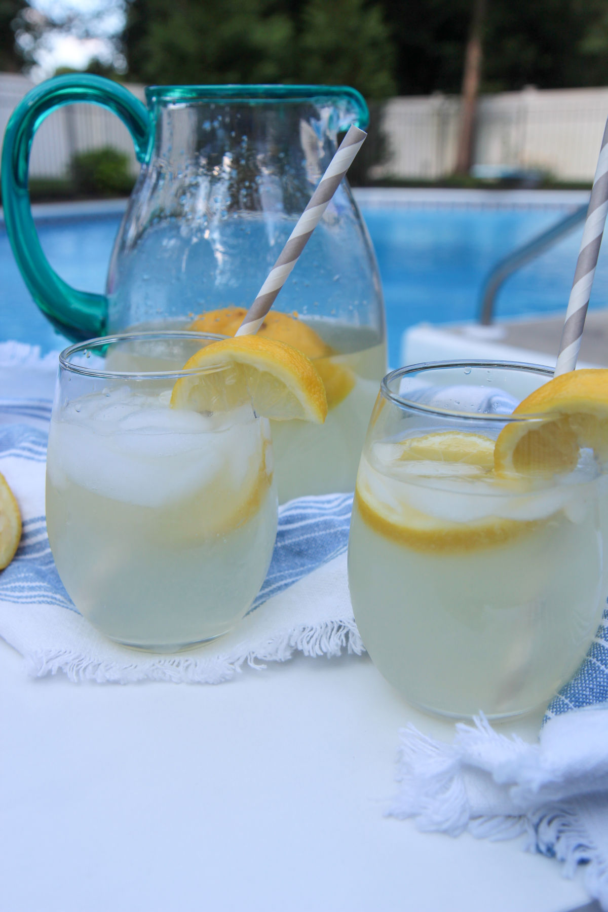 two glasses of lemonade and a glass pitcher in the background