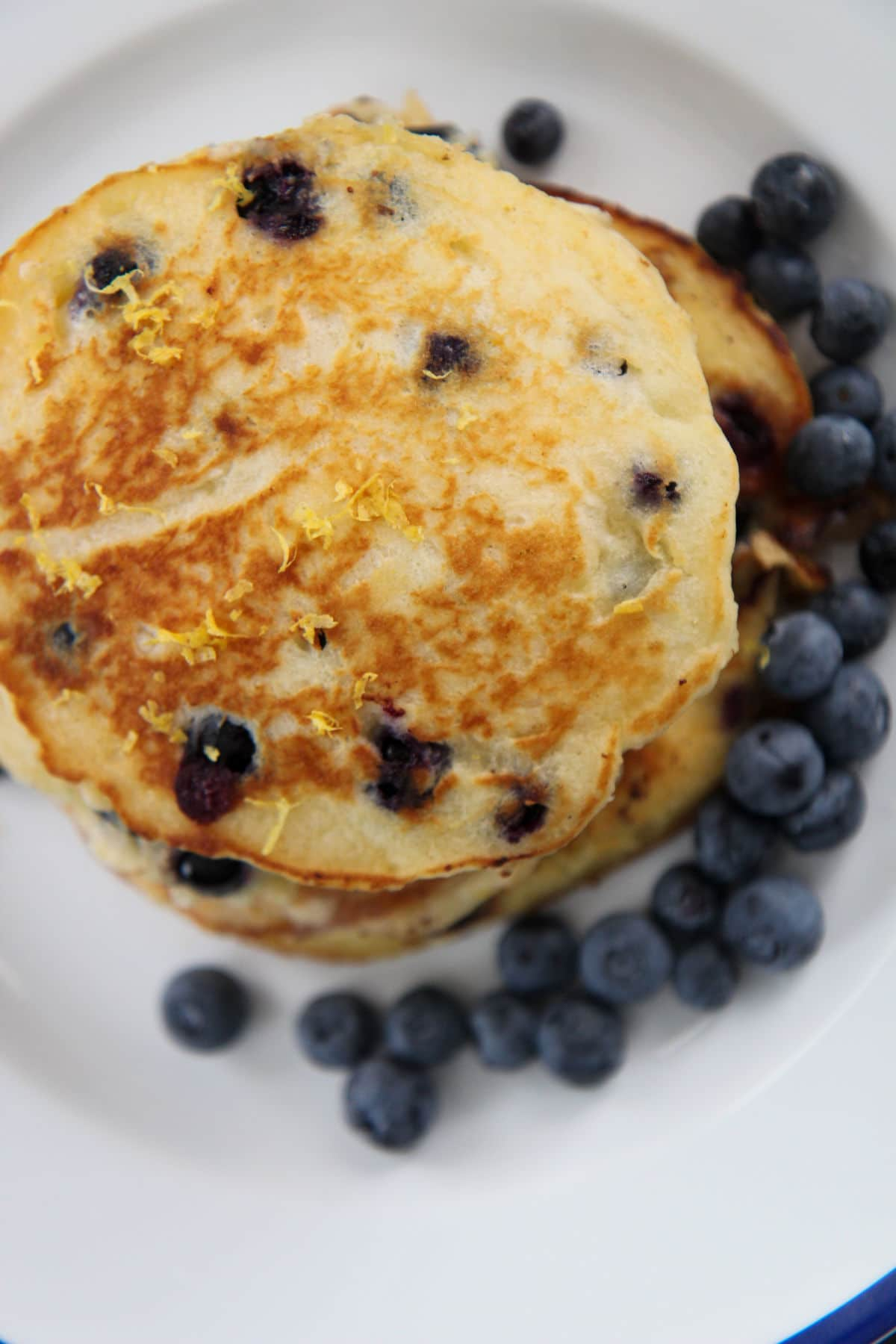 stacked blueberry pancakes on a white plate with blueberries on the side
