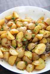 baby yellow potatoes in a white bowl with a aspoon
