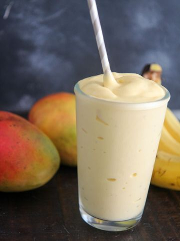 mango smoothie in a glass with a straw and fruits in the background