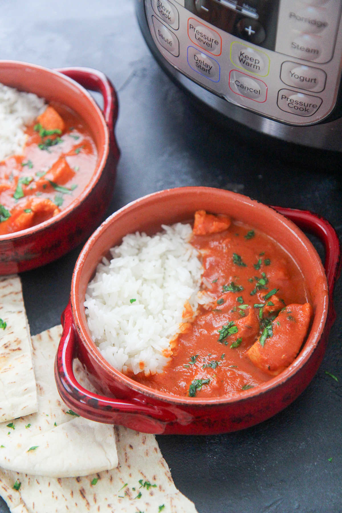 two small bowls with butter chicken and pita bread