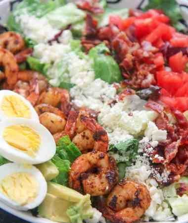 shrimp cobb salad with boiled eggs in a white plate