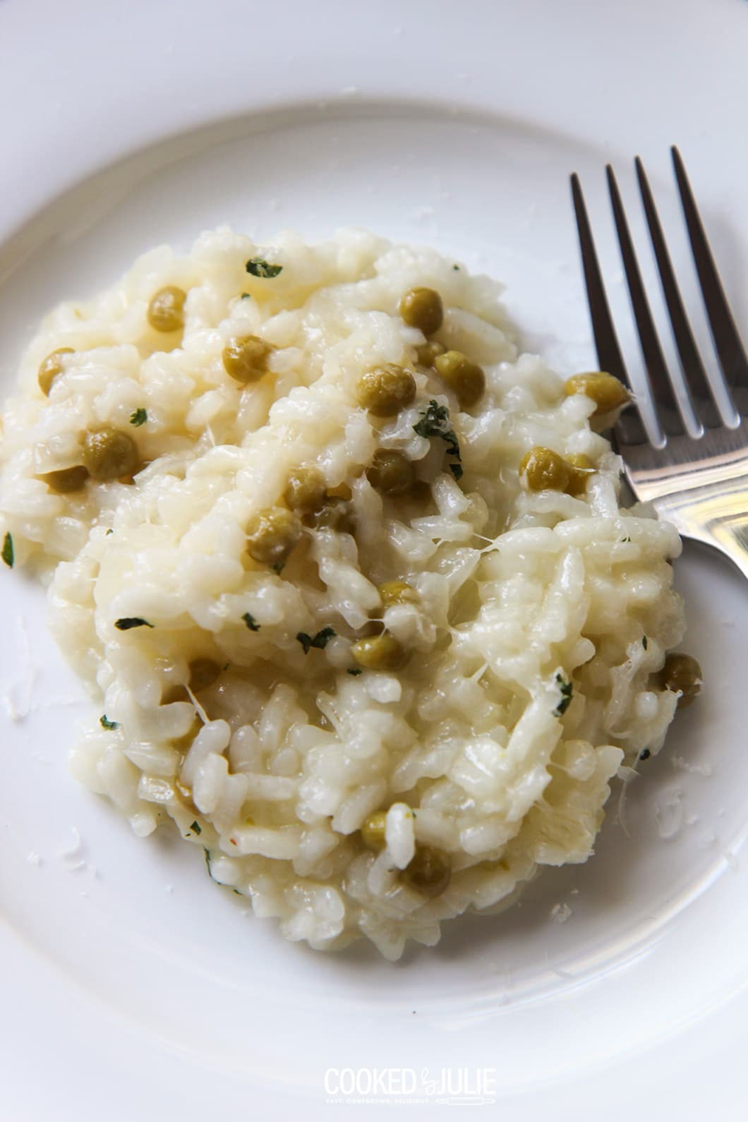 parmesan risotto on a white plate with a fork