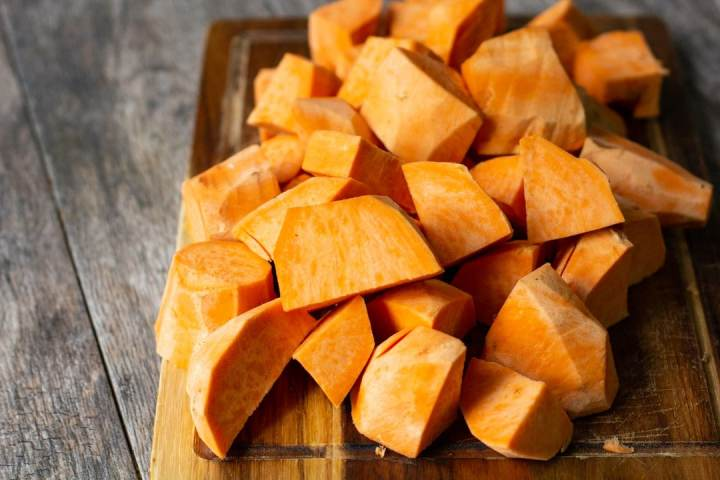 chopped up sweet potatoes on a wooden board