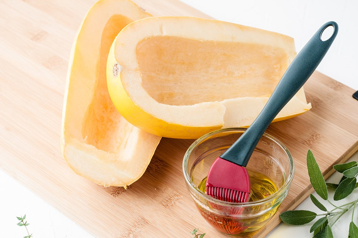 yellow squash on a wooden board with olive oil on the side