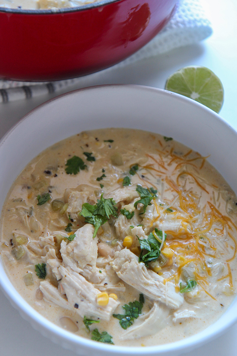 white chicken chili in a white bowl with lime on the side