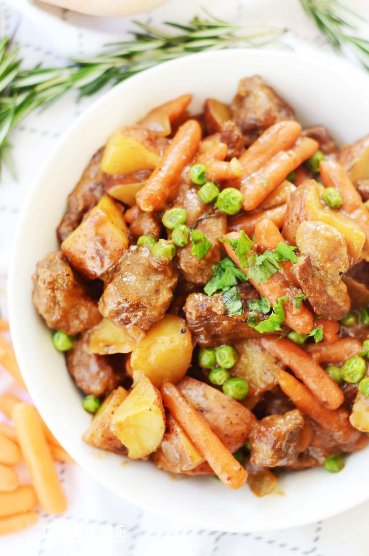 beef stew with parsley in a white bowl and a sprig of rosemary