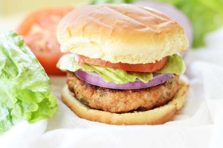 salmon burger with lettuce, onion, and tomato, up close