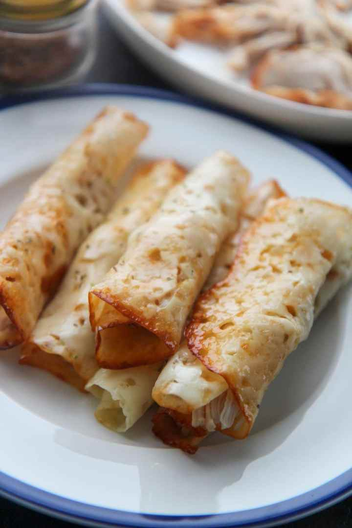 six keto cajun chicken taquitos on a white and blue plate