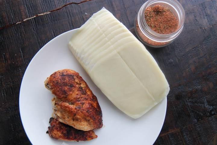 cooked chicken breast, cajun seasoning in a jar, and mozzarella slices.