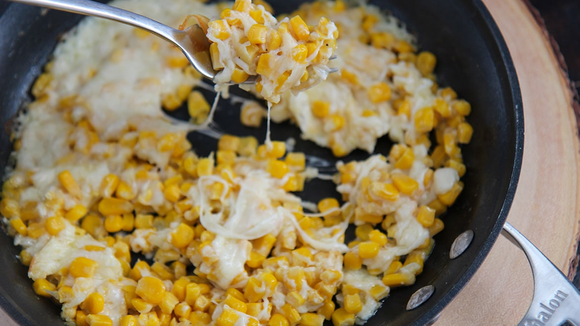a fork, cheese, and corn in a black skillet.