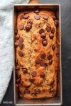 chocolate chip banana bread in a load pan on a black surface with a blue towel on the side.