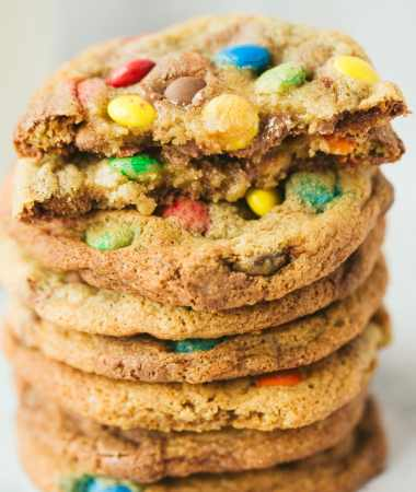 eight m&m cookies stacked on top of each other. One cookie is cut in half.