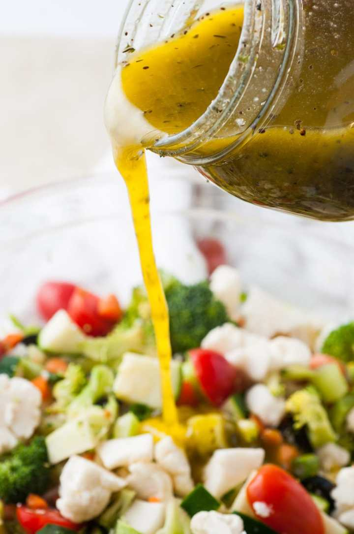 dressing poured over a bowl of vegetable salad.