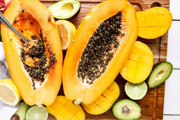 a papaya cut in half with avocados and mangoes on the side.