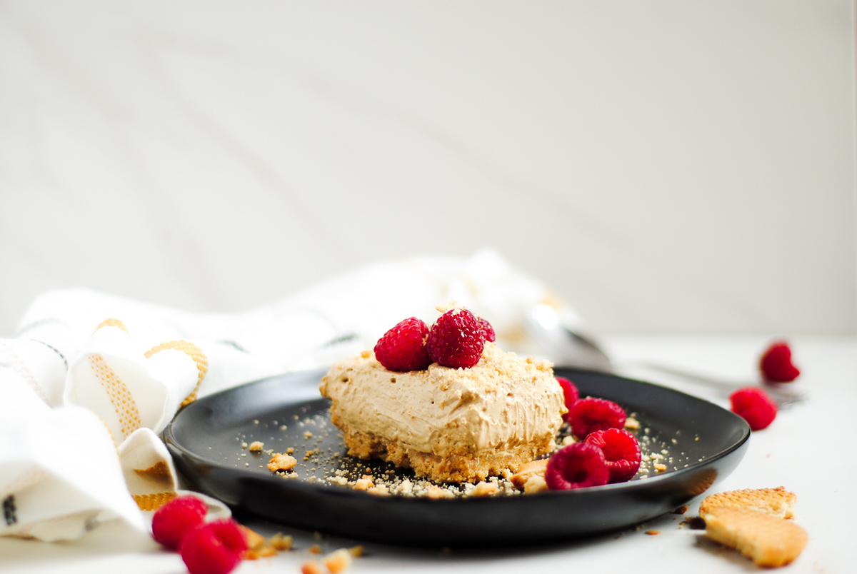 a horizontal up close shot of a slice of dalgona cheesecake on a black plate with crushed cookies and raspberries.