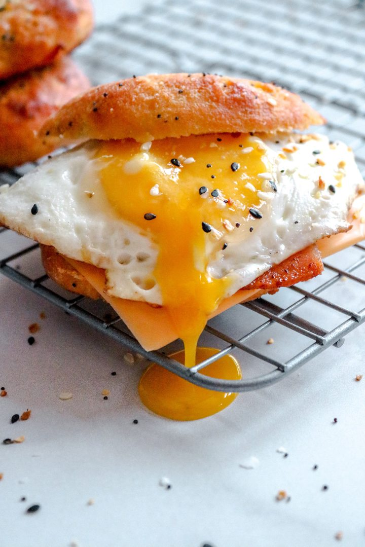 an up close shot of the keto breakfast sandwich with a runny egg on top of a wire rack.