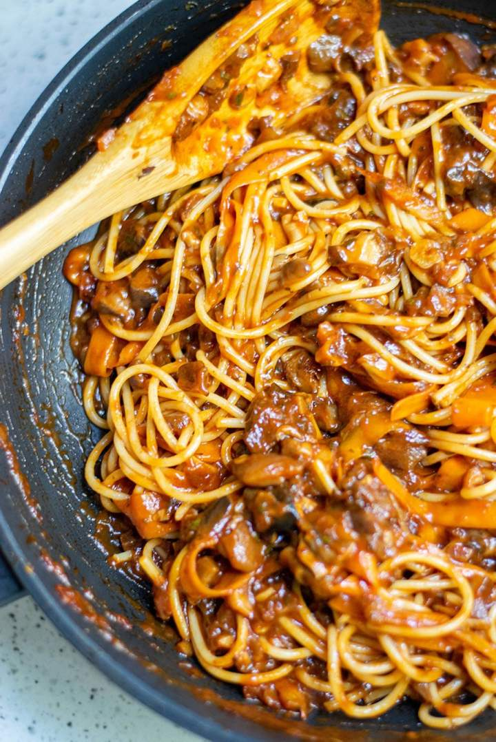 mushroom bolognese with pasta and a wooden spoon in a black skillet.