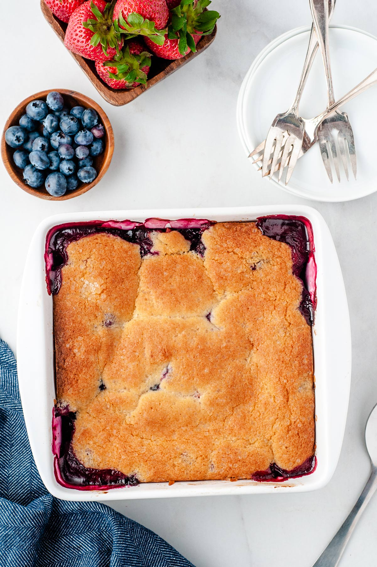 berry cobbler in a white baking dish with strawberries and blueberries on the side. Forks and a small plate on the side.