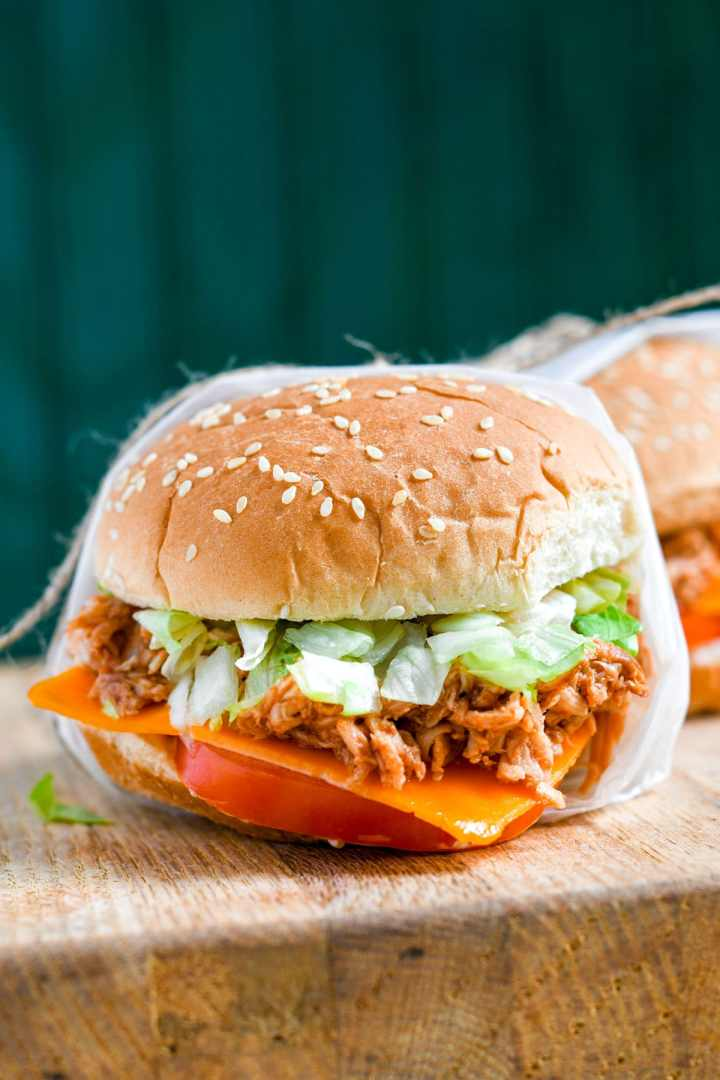 a shredded chicken sandwich on a wooden board and a green backdrop.