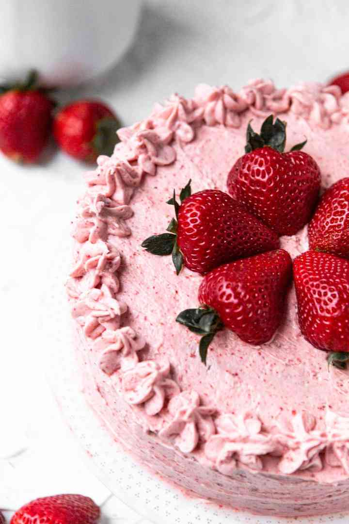 half of an entire strawberry cake with fresh strawberries on top and on the side.