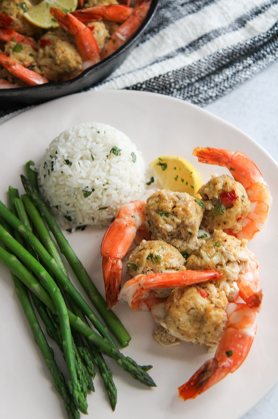 white rice, asparagus, and stuffed shrimp on a white plate.