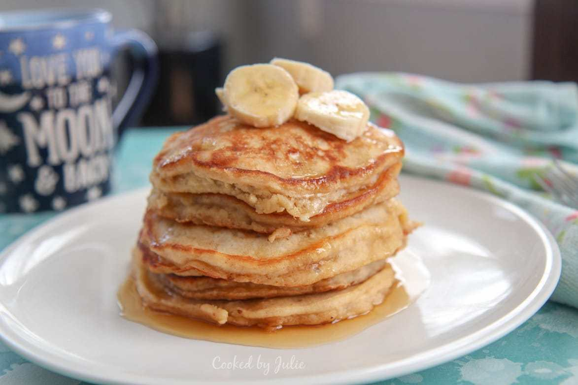 short stack of banana pancakes on a white plate.
