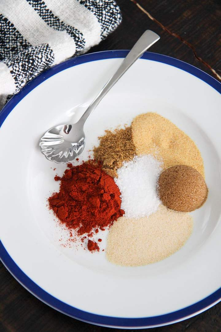 brown sugar and 5 spices on a white plate with a small spoon and towel on the side.