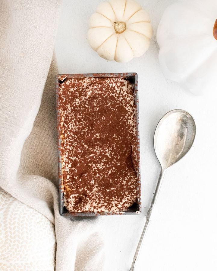tiramisu in a loaf pan with a dark topping, a silver spoon, a light towel, and a white pumpkin on the side.