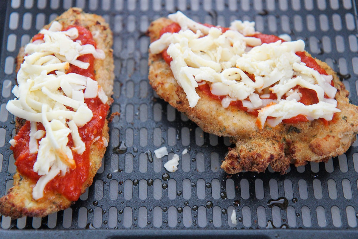 two chicken breasts with sauce and shredded cheese on top.