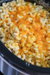 mac and cheese in the crockpot with yellow melted cheese on top