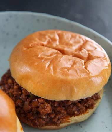 a sloppy joe up close on a blue plate.